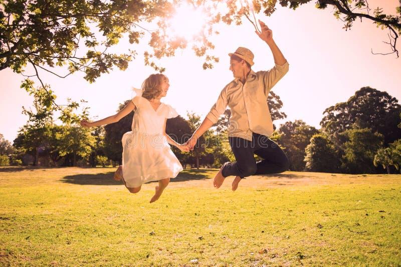 Śliczny pary doskakiwanie w parku wpólnie trzyma ręki ilustracji