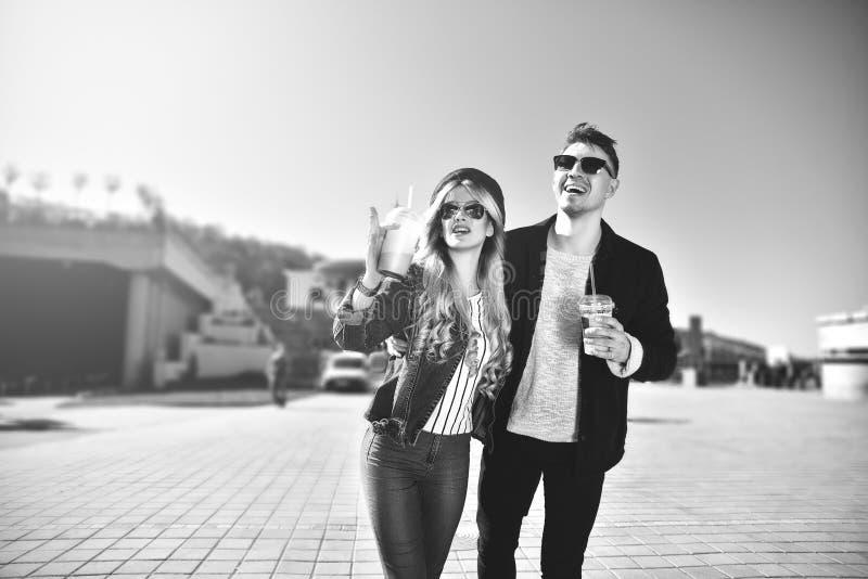 Śliczny pary odprowadzenie przy ulicą i pije koktajle fotografia stock