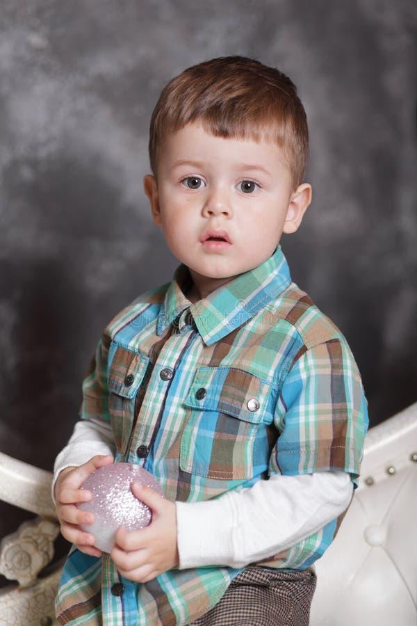 Śliczny portret chłopiec świętuje boże narodzenia Chłopiec bawić się decoraction piłkę fotografia royalty free