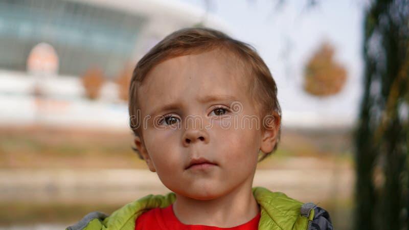 Śliczny poważny chłopiec portret outdoors w parku obrazy stock