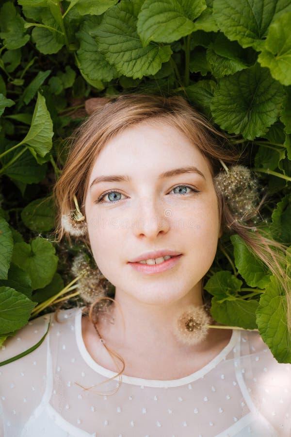 Śliczny powabny młodej kobiety lying on the beach na zieleni dandelions i liściach fotografia stock