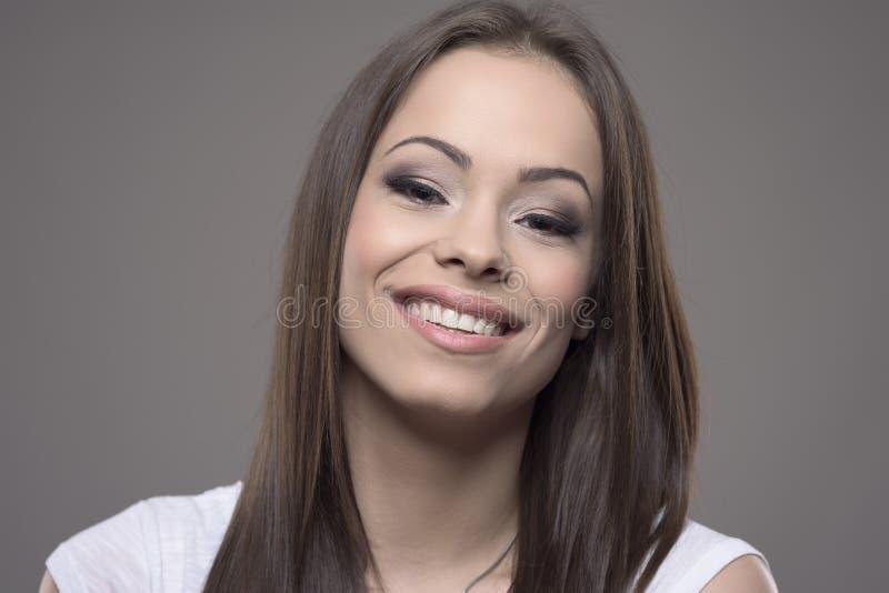 Śliczny powabny młody żeński uśmiechnięty i patrzeje kamery twarzy zbliżenie fotografia stock
