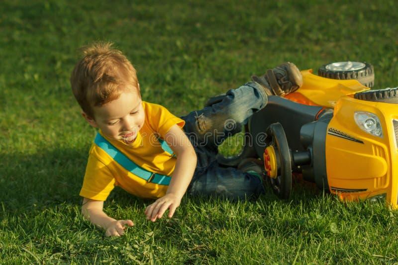 Śliczny pozytywny dzieciak, bawić się szczęśliwie z dziecko samochodem na zielonej łące obraz royalty free