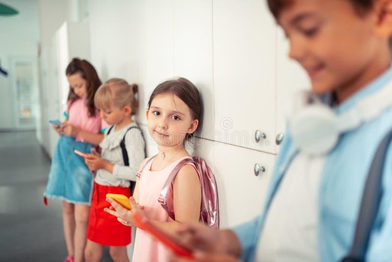 Śliczny przyglądający się dziewczyny mienia telefon podczas gdy stojący blisko przyjaciół fotografia stock