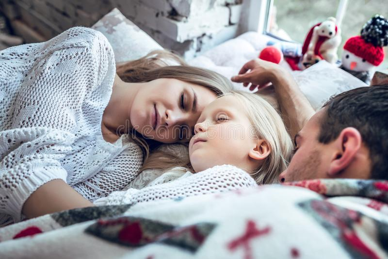 Śliczny rodzinny dosypianie wpólnie w łóżku zdjęcie stock