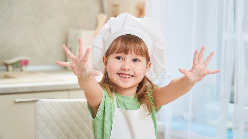 śliczny roześmiany dziecko kucharz macha jego ręki nadużyte za jego rękach i otwierać jego palmy pokazuje szczęście, zdjęcia royalty free
