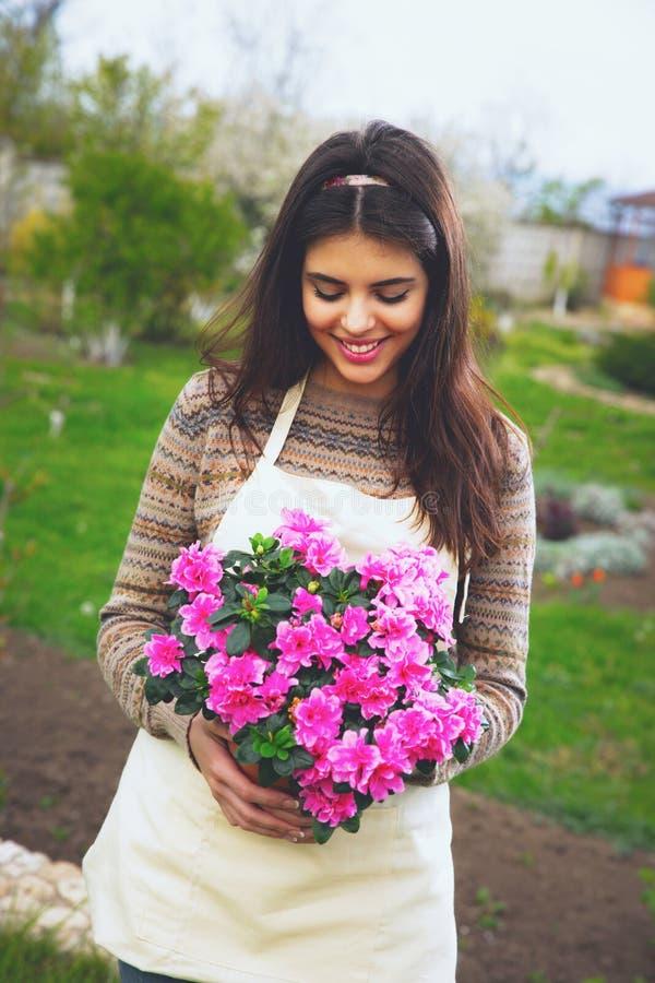 Śliczny rozochocony kobiety mienia kwiat w garnku zdjęcia stock