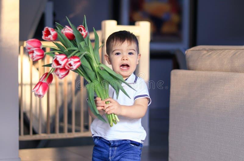 Śliczny szczęśliwy chłopiec mienia bukiet czerwoni tulipany w jego rękach wita matki, siostra lub babcia w domu Matki lub dolina obrazy royalty free