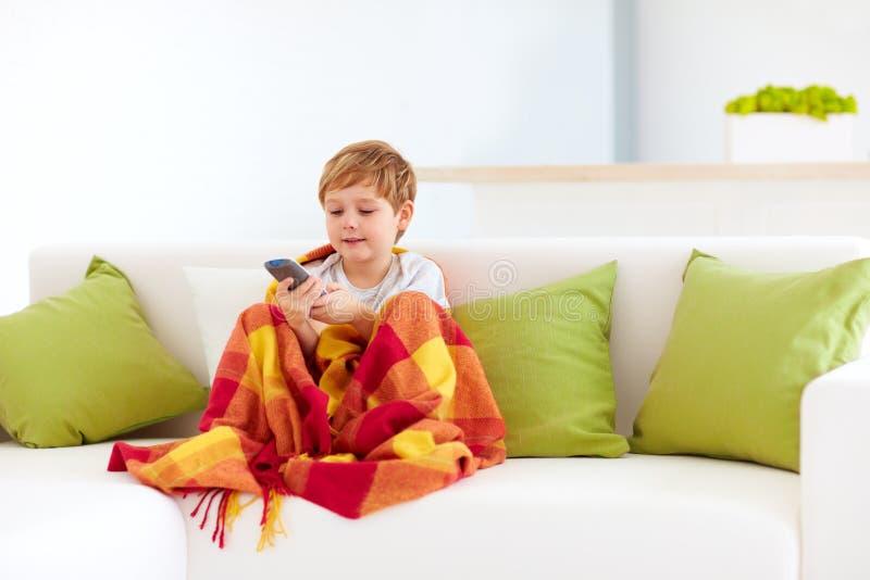 Śliczny szczęśliwy dzieciak ogląda tv w domu zdjęcie stock
