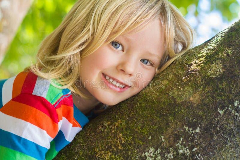 Śliczny szczęśliwy, uśmiechnięty dziecko relaksuje outdoors w drzewie, obraz royalty free