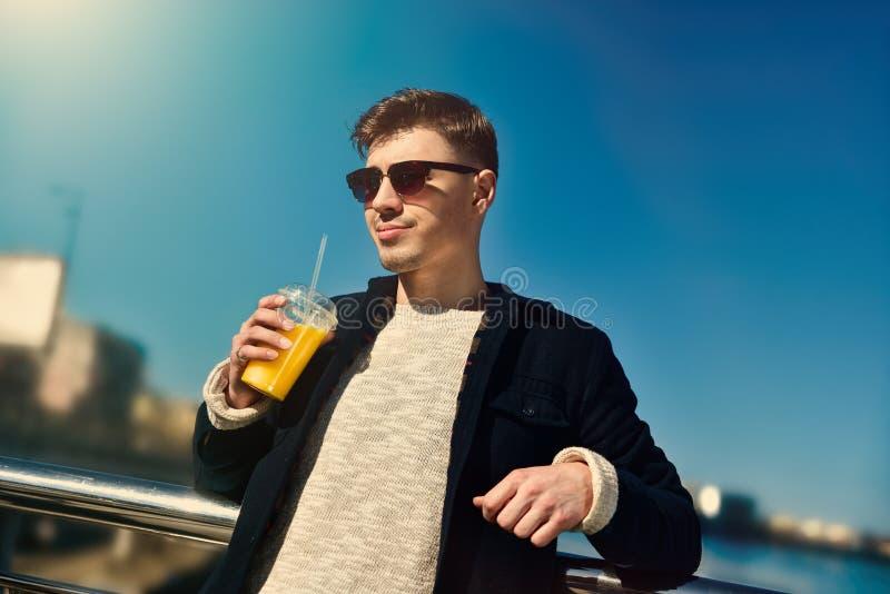 Śliczny uśmiechnięty mężczyzna chwyt sok przy miastem zdjęcie royalty free