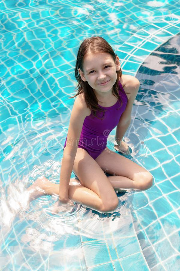 Śliczny uśmiechnięty preteen dziewczyny obsiadanie przy basen krawędzią Podróż, wakacje, dzieciństwo zdjęcia stock