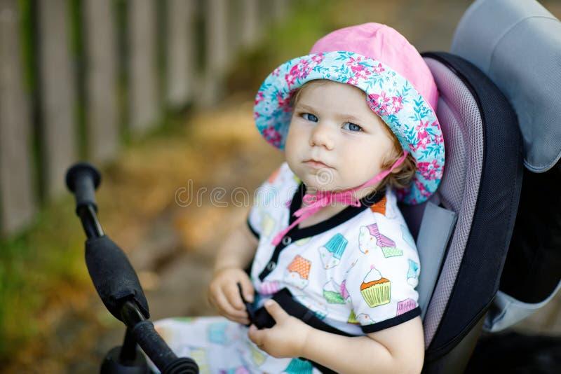 Śliczny uroczy berbeć dziewczyny obsiadanie na dosunięcie trójkołowu lub bicyle Mały dziecka dziecko iść dla spaceru z rodzicami  fotografia royalty free