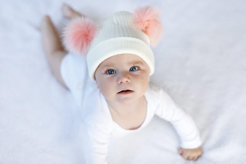 Śliczny uroczy dziecka dziecko z ciepłym białym i różowym kapeluszem z ślicznym bobbles zdjęcie stock