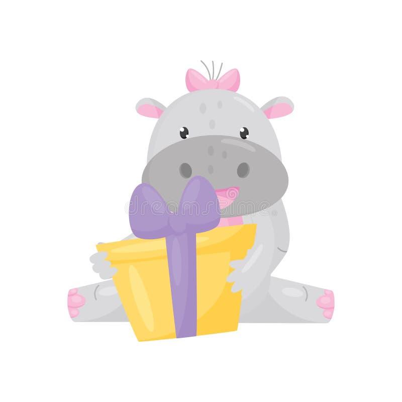Śliczny uroczy hipopotam z różowym łęku mienia i obsiadania prezenta pudełkiem, uroczego behemotu postaci z kreskówki zwierzęcy w royalty ilustracja