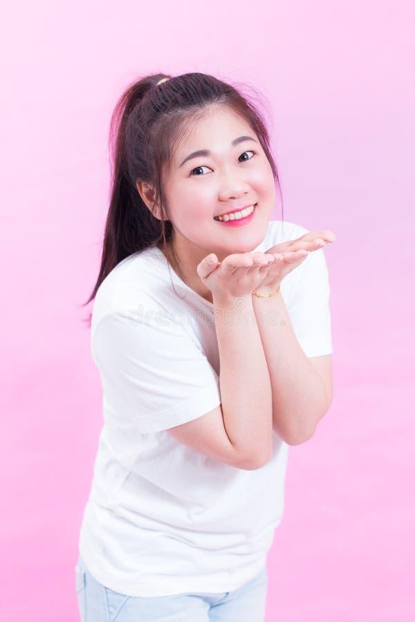 Śliczny uroczy piękna młoda azjatykcia kobieta czarni włosy odzież dosłanie buziak nad różowym tłem i obrazy stock