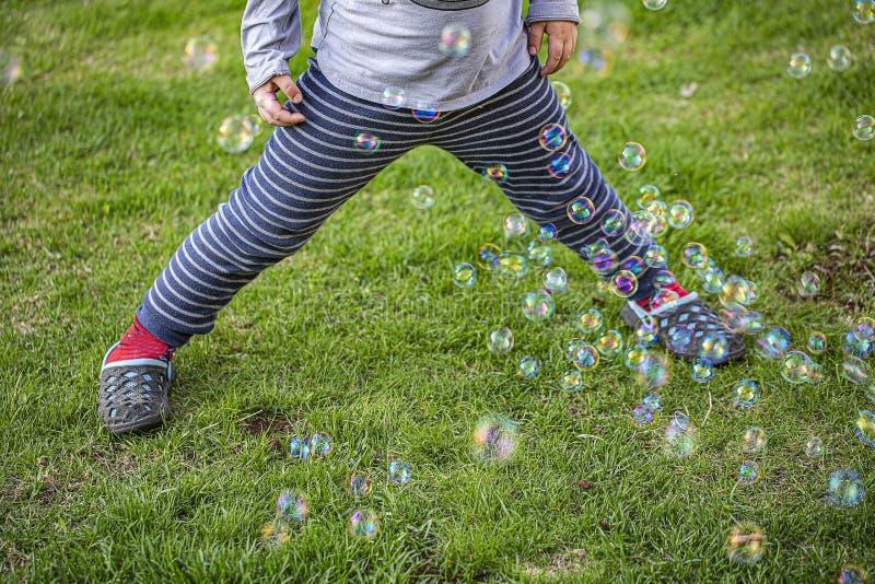 Śliczny widok dziecko postaci kursowanie z kolorowymi bąblami na zielonym gazonie Pi?kni t?a obraz royalty free