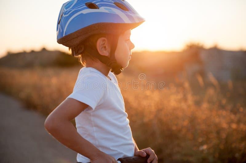 Śliczny zdrowy dziecko w sporta hełmie z hulajnoga na pustej drodze na zmierzchu zdjęcia stock