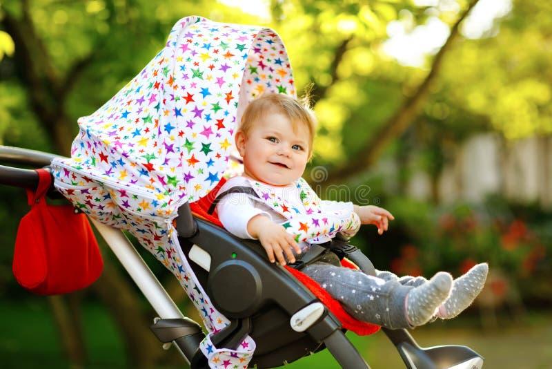 Śliczny zdrowy mały piękny dziewczynki obsiadanie w czekać na mamie, pram i spacerowiczu lub Szczęśliwy uśmiechnięty dziecko z obraz royalty free