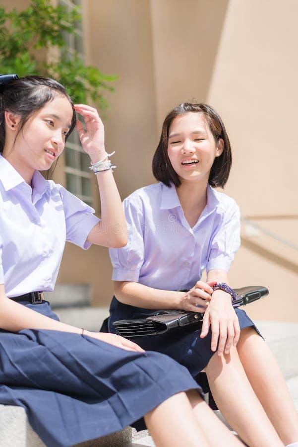 Ślicznych Azjatyckich Tajlandzkich wysokich uczennic studencka para w mundurku szkolnym siedzi na schody gawędzeniu z szczęśliwym obraz royalty free
