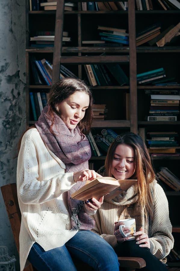 Ślicznych studenckich przyjaciół czytelnicze książki ma zabawę zdjęcie stock