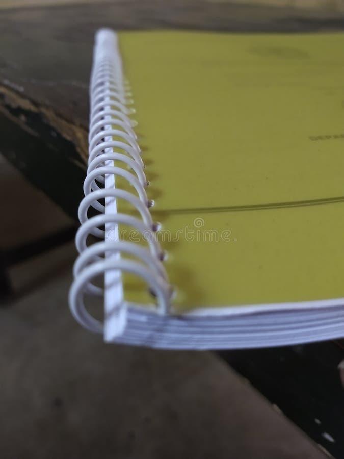 Ślimakowata kartoteka z kolor żółty pokrywą nad nim i dziurami na papierze zdjęcie stock