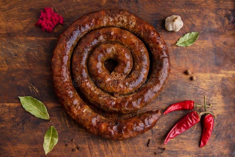 Ślimakowaty kiełbasa pierścionek piec w starym piekarniku jest na drewnianej desce z pieprzem i czosnkiem zdjęcia stock
