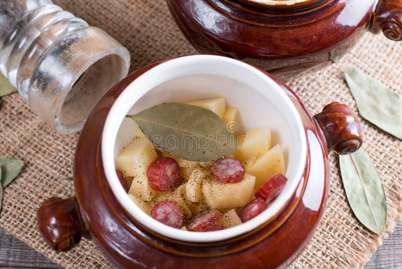Śliskiej sprawy goulash z bekonem i Wiedeń kiełbasami słuzyć w ceramicznym pucharze z starym drewnianym stołem dalej obraz royalty free