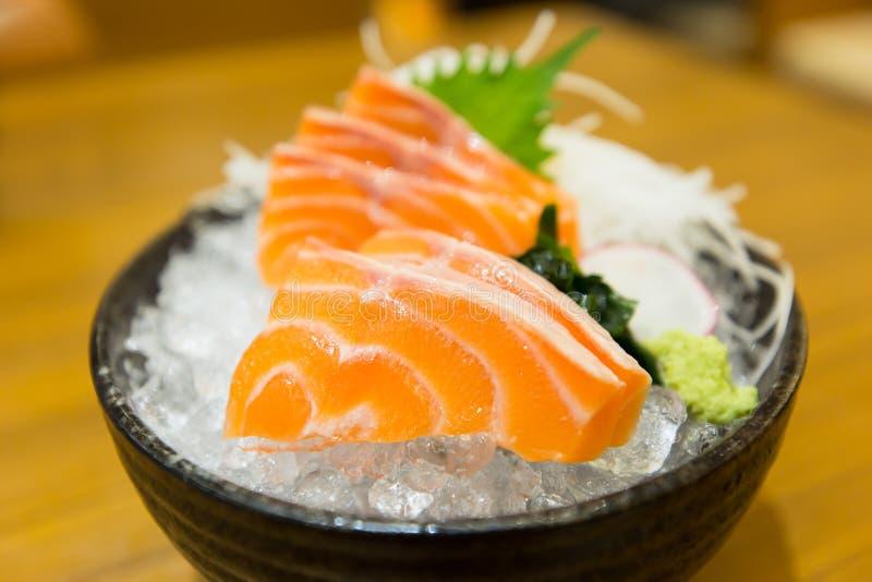 Ślizga się łososiowego sashimi na lodzie w czarnym pucharze zdjęcia royalty free