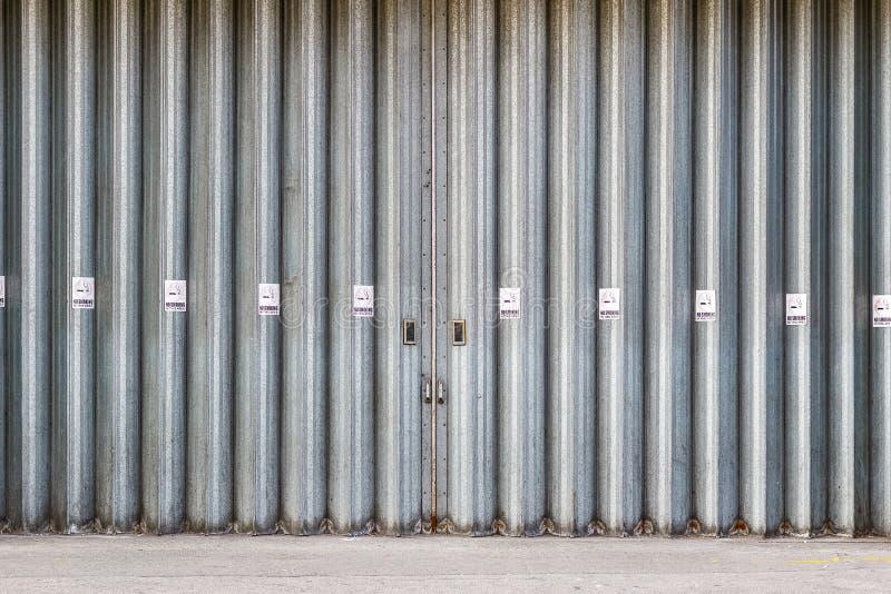 Ślizgający się przemysłowych drzwi z Palenie Zabronione znakami i składający obraz royalty free