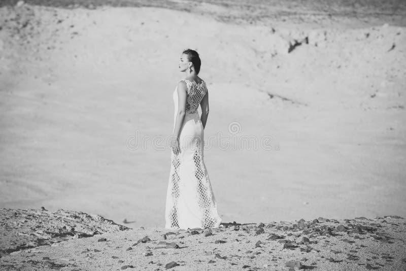 Ślubna agencja Kobieta w biel sukni pozyci na piasek diunach w pustyni obrazy stock