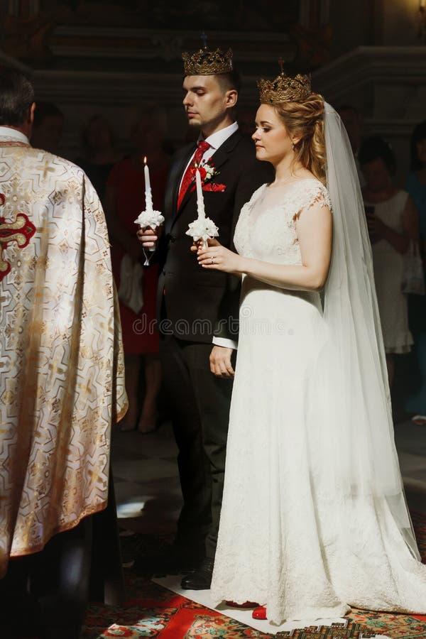 Ślubna ceremonia przy kościół elegancki fornala i panny młodej mienia cand zdjęcie stock