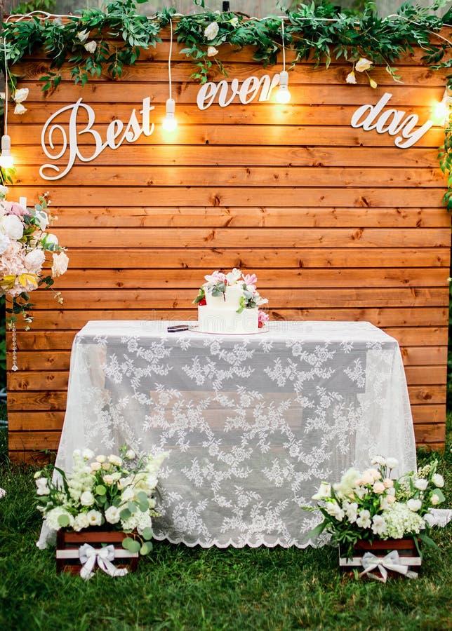 Ślubna ceremonia w pięknym ogródzie z stołem zakrywającym z białym tablecloth zdjęcie stock