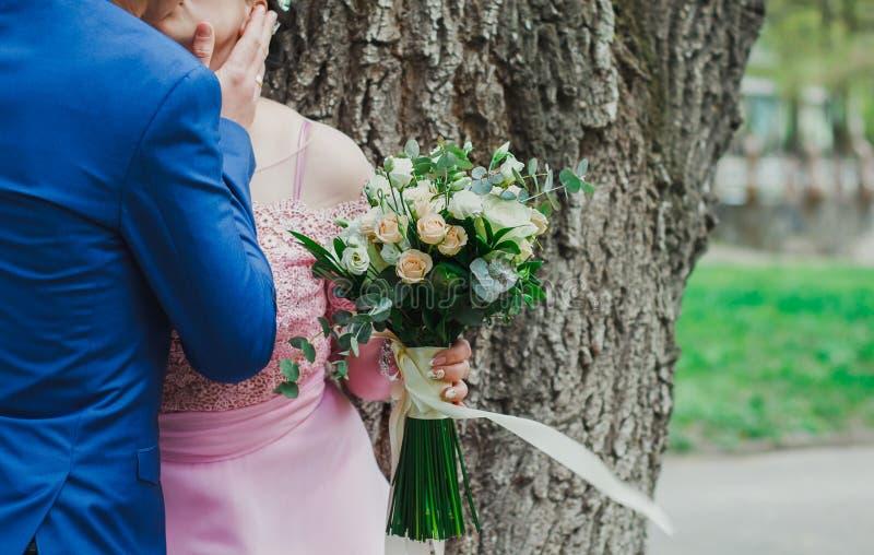 Ślubna para całuje blisko drzewa w zielonym parku lub lesie Plus wielkościowa panna młoda w menchii koronce suknia trzyma bukiet  obrazy royalty free