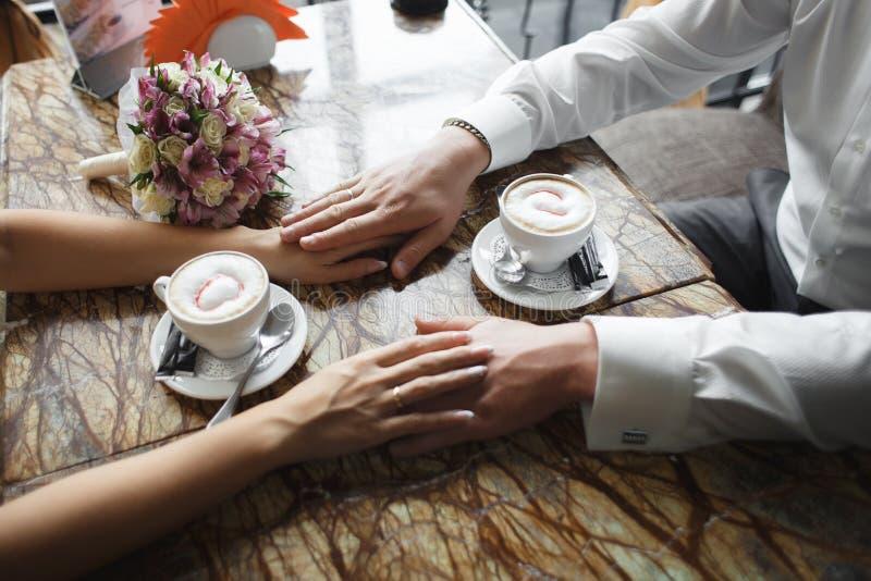 Ślubna para przy kawiarnią Mężczyzna trzyma kobiety rękę, pije cappuccino Państwo młodzi kawowej przerwy datowanie prezent, bukie zdjęcie stock