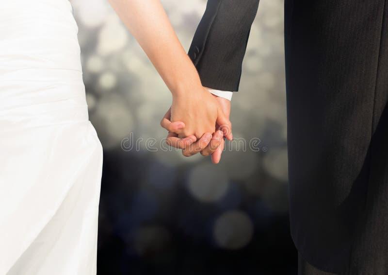 Ślubne pary mienia ręki przeciw jarzyć się światła obrazy stock