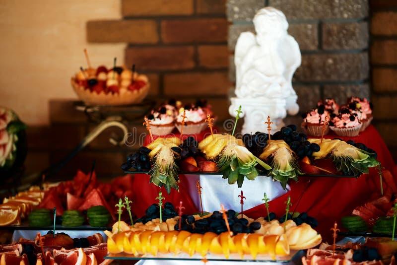 Ślubne różnorodne świeże owoc, jagody z smakowitym colour i desery w filiżankach różowa śmietanka na bufeta stole z dekoracjami obrazy royalty free