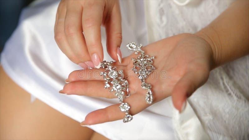 Ślubni kolczyki na bridal ręce, akcesoria i dekoraci pojęcie, panny młodej ` s biżuterii i ranku Dziewczyna chwyta kolczyki obrazy stock