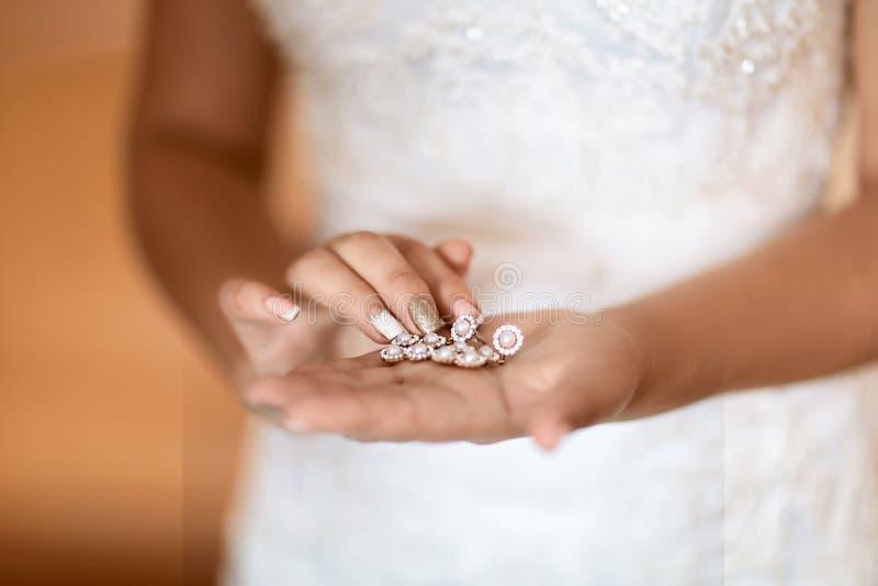 Ślubni kolczyki na bridal ręce, akcesoria i dekoracji pojęcie, panna młoda ranku i biżuterii, selekcyjna ostrość fotografia royalty free