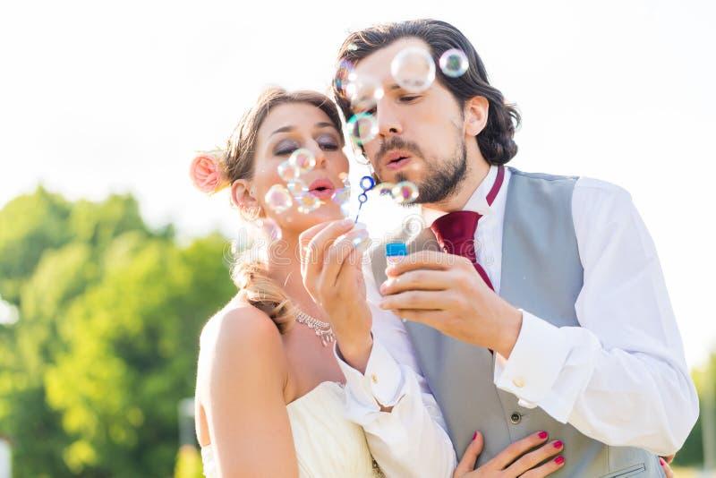 Ślubni państwa młodzi dmuchania bąble zdjęcia stock