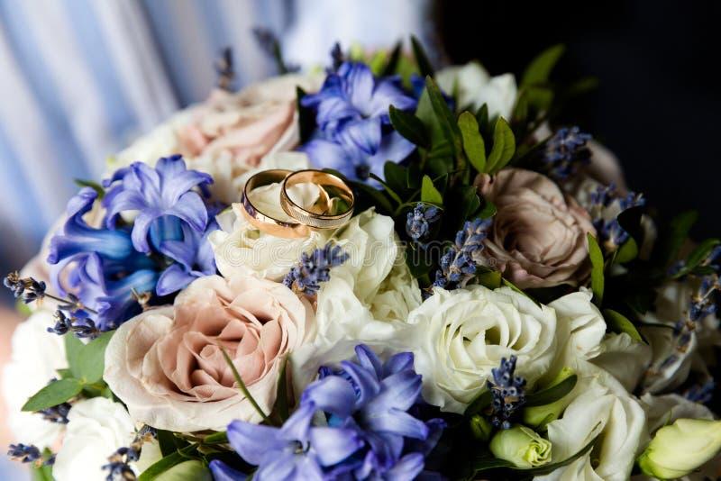 Ślubni złociści pierścionki na bukiecie kwiaty obrazy royalty free