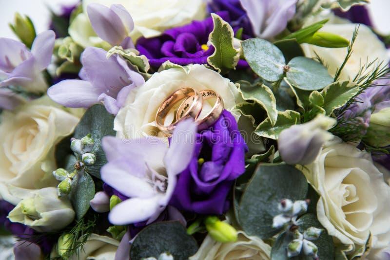 Ślubni złociści pierścionki na bukiecie kwiaty obraz royalty free