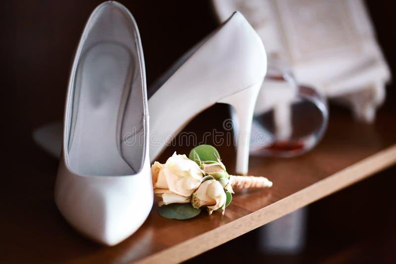 Ślubny akcesoria bukieta beż kwitnie dla fornala i bielu butów na piętach, ciemny drewniany tło, ranek panna młoda fotografia royalty free