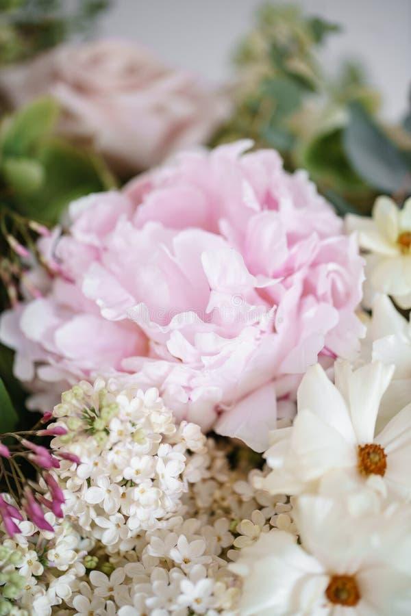 Ślubny bukiet bez, róże, peonia i jaskier na drewnianym stole biali, Udziały greenery, nowożytny asymmetrical obraz royalty free