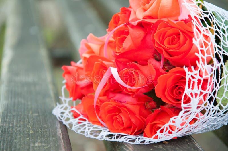 Ślubny bukiet czerwone róże kłama na ławce Fragrant kwiaty, wąchają pięknego zdjęcia royalty free