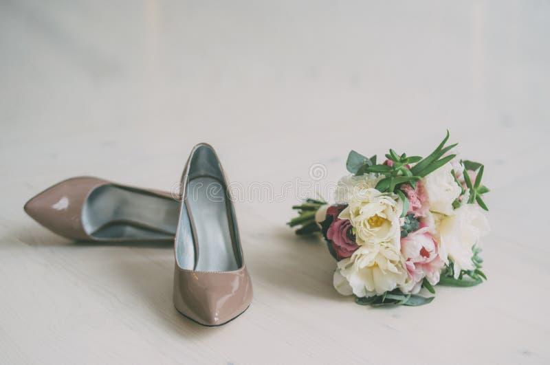 Ślubny bukiet kwiaty i beżowi ślubów buty zdjęcia royalty free