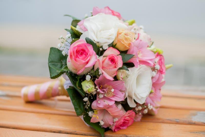 Ślubny bukiet kwiaty kłama na ławce na zamazanym tle, fotografia stock