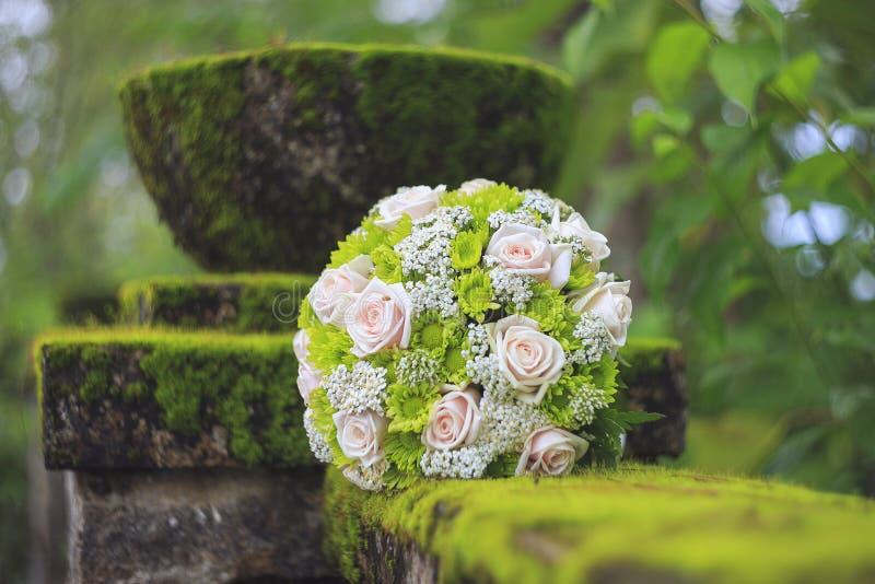 Ślubny bukiet na mech zakrywającym betonu ogrodzeniu fotografia stock