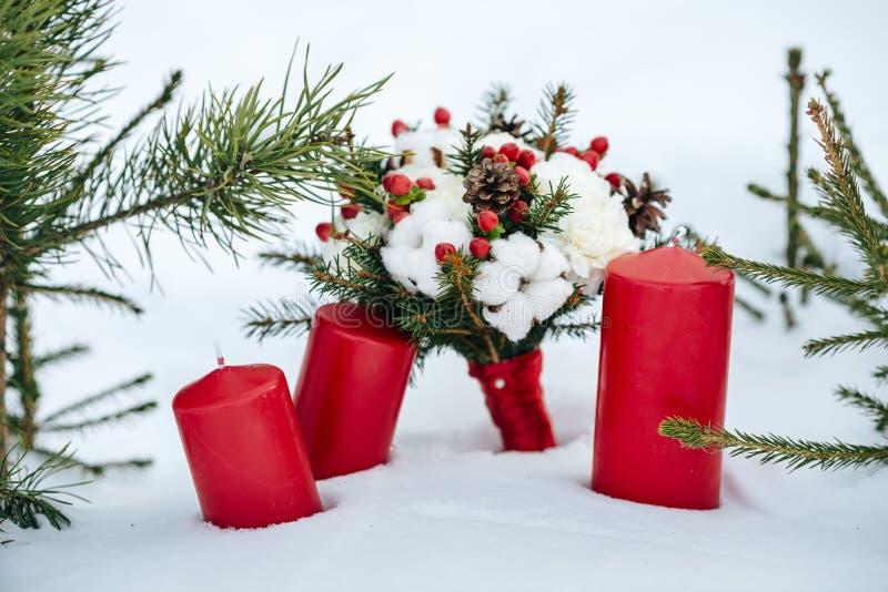 Ślubny bukiet z bawełną i jedlinowymi gałąź, czerwone świeczki stoi w śniegu zdjęcie stock