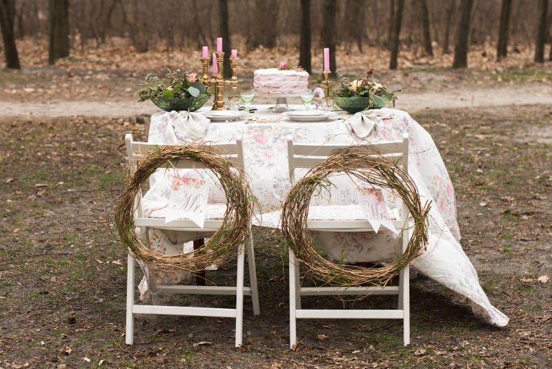 Ślubny dekoracja stół w ogródzie, kwiecisty przygotowania W stylowym roczniku słuzyć dla dwa ludzi na plenerowym, fotografia royalty free